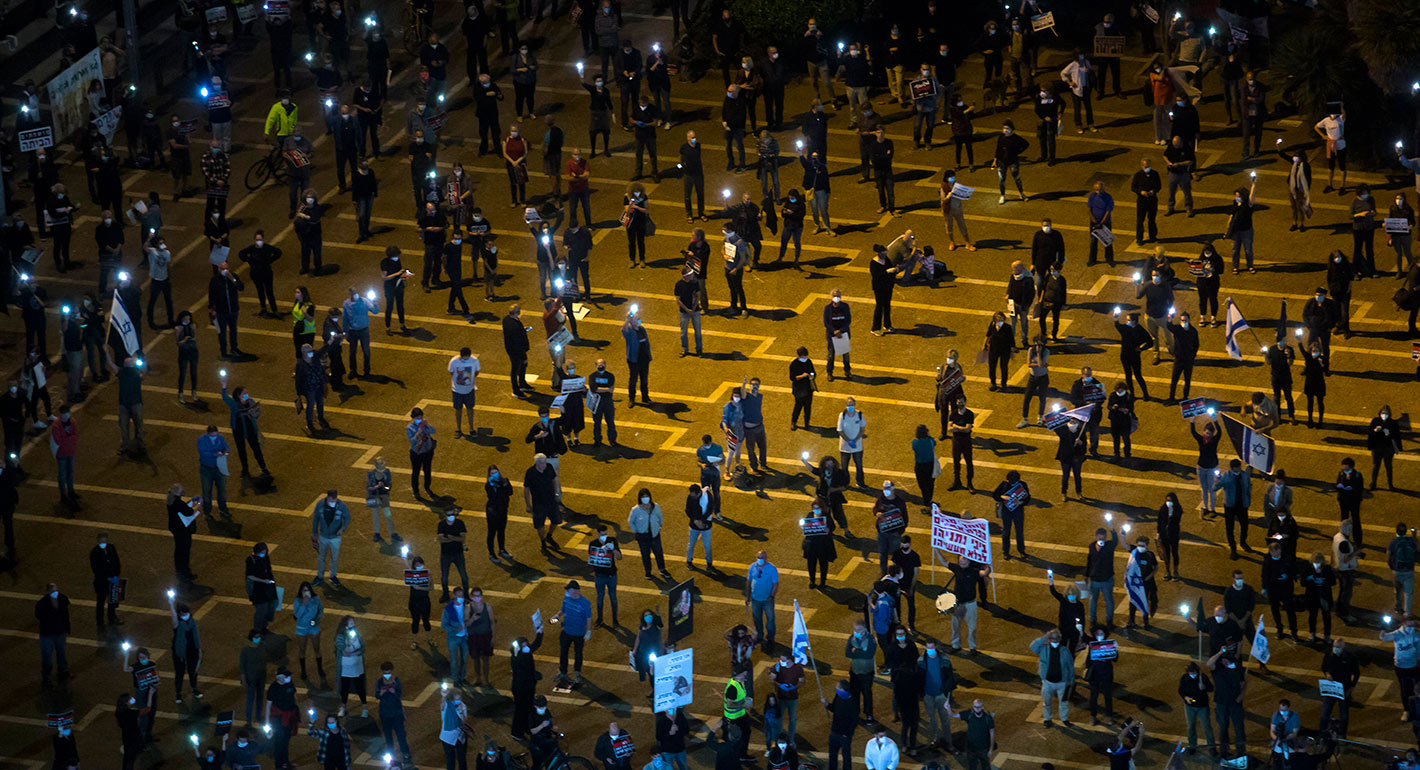 Israelis light flash lights as they protest at an Anti-Corruption rally under coronavirus restrictions in Rabin Square on April 19, 2020 in Tel Aviv, Israel