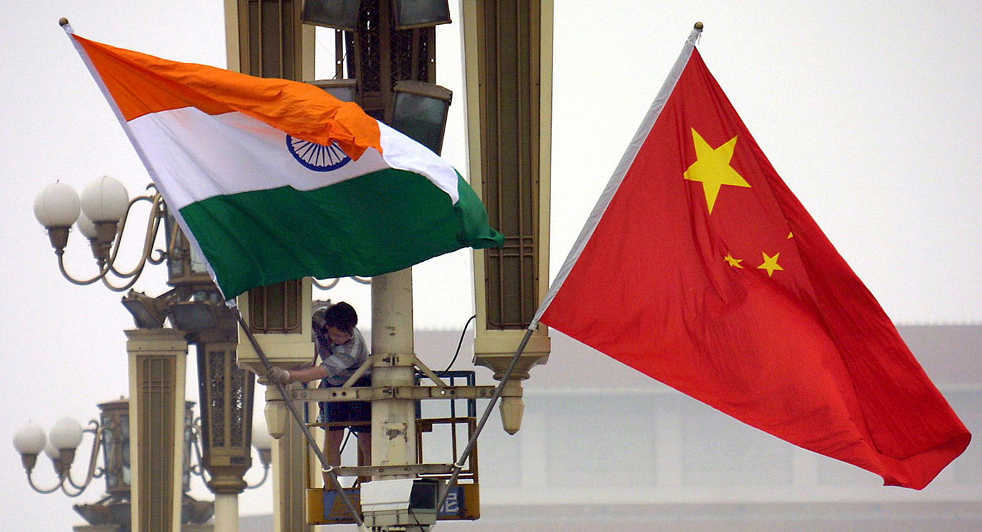 Workers put up the Indian flag (L) alongside the Chinese flag on Tiananmen Square in Beijing