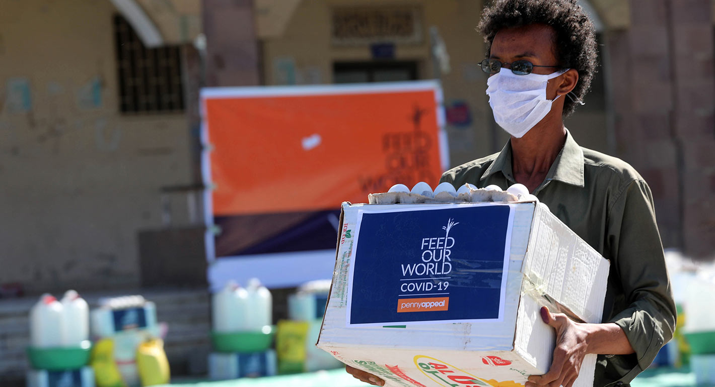 A man wearing a protective mask receives humanitarian aid in Yemen's third city of Taez