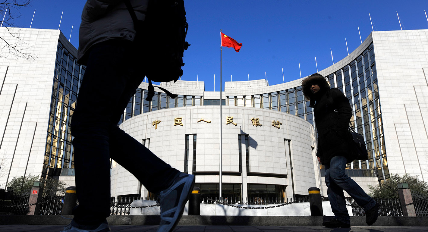Two pedestrians walk in front of the headquarters of the People's Bank of China in Beijing