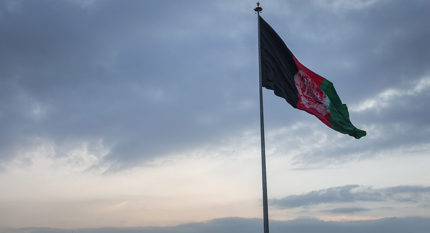 Residents pass an Afghan flag flying on a hill top in Kabul, Afghanistan, on Friday, Nov. 17, 2017.