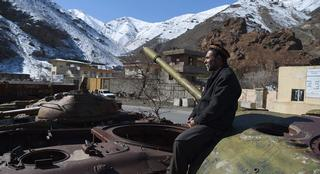 An Afghan man sitting on the remains of Soviet-era tanks along a road