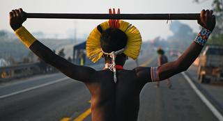 A member of the Kayapo tribe walks along the middle of blocked highway BR163 during a protest