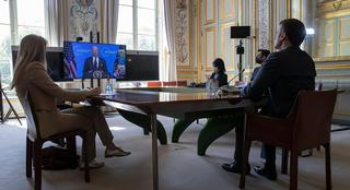 French President Macron listens to US President Biden (on screen) during a virtual summit