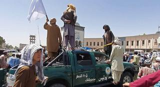 Taliban fighters stand over a damaged police vehicle along the roadside in Kandahar on August 13, 2021