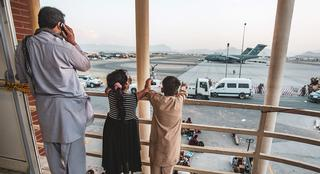 an Afghan family looks over Hamid Karzai International Airport during the evacuation, August 2021