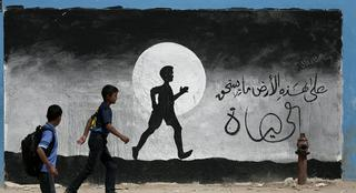 Two Palestinian schoolboys walk past a graffiti painted on a wall of a UN school in Gaza
